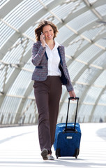 Business woman walking at station with bag and mobile phone