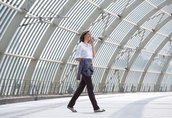Business woman walking and talking on mobile phone