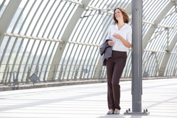 Business woman standing at station with mobile phone