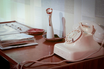 Retro desk. An retro scene of an old 1950's telephone in a contemporary setting with phone book on a side table.