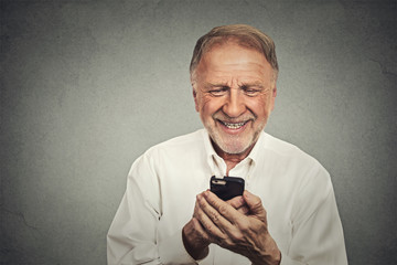 elderly man looking at his smart phone while text messaging
