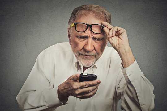 elderly man with glasses having trouble seeing cell phone