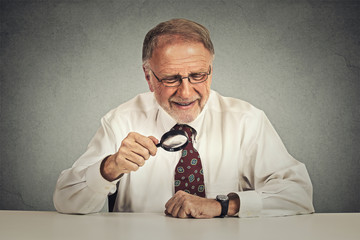 Senior businessman looking through a magnifying glass