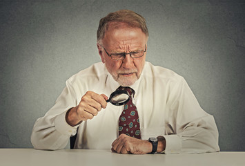 Senior grumpy businessman looking through magnifying glass