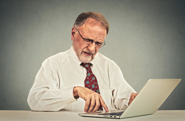 Confused senior man working on laptop computer