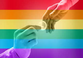 close up of male gay couple hands giving condom