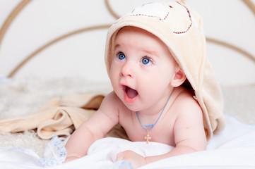 Little baby smiling under bath towel