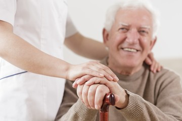 Senior man and helpful nurse
