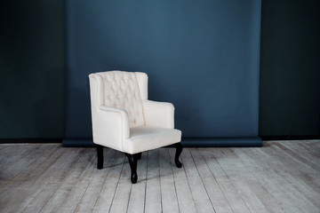 One classic armchair against a dark blue wall and floor. Copy