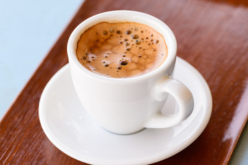 Hot espresso in white cup on wooden tray.