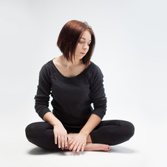 young beautiful woman sitting in lotus position, closeup