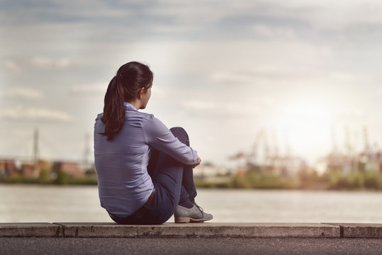 Thoughtful Woman Sits on Bench Facing at the River
