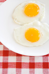 Two Fried Eggs on Plates – Two fried, sunny side up eggs on a white plate. Red checked background.