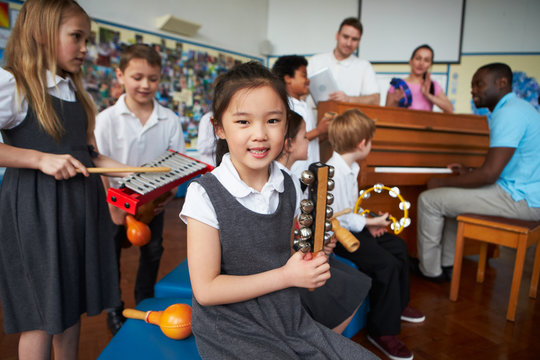 Group Of Children Playing In School Orchestra Together