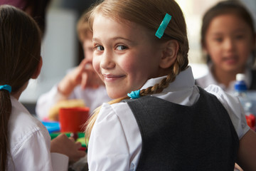 Girl Eating Healthy Packed Lunch In School Cafeteria