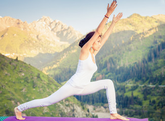 Inspired asian woman doing exercise of yoga at mountain range of Kazakhstan. She dressed in white sportswear.