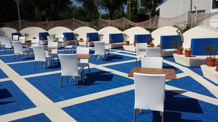 Empty restaurant under the open sky. All in white, blue, brown.