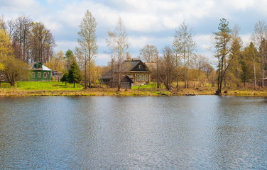 Spring landscape with wooden houses on the river bank