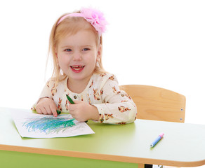 Little Caucasian blond girl draws with pencils sitting