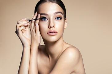 Woman applying black mascara on eyelashes with makeup brush / photos of appealing brunette girl on beige background