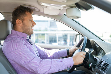 Successful businessman is sitting at steering wheel