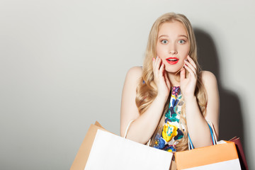 Pretty young woman is showing her surprise about prices