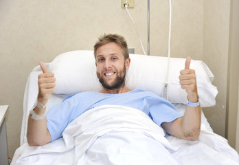young American man lying in bed at hospital room sick but happy