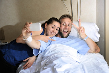 young couple taking selfie photo at hospital room with man in bed