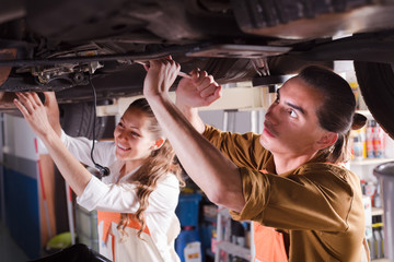 Two mechanics repairing car