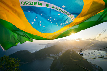 Brazilian flag shines above the golden sunset city skyline at Sugarloaf Pao de Acucar Mountain in Rio de Janeiro Brazil