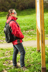 Mid adult woman with backpack, in park reading map