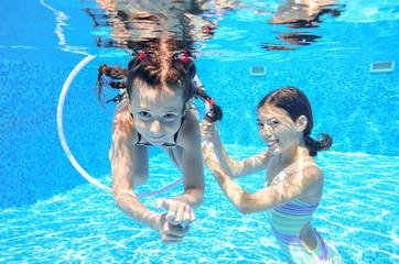 Happy children swim in pool underwater, girls swimming, playing and having fun