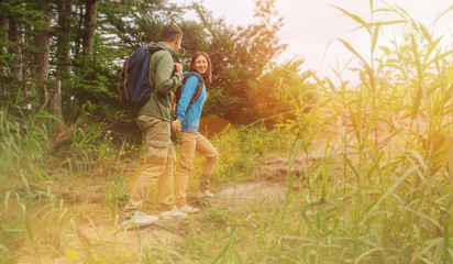 Hiker young couple walking in summer forest