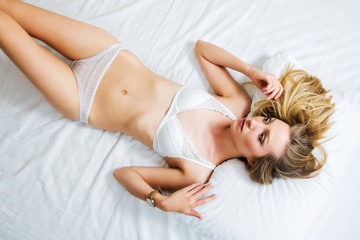 Sexy girl in white lace underwear lying on the bed, emotive portrait