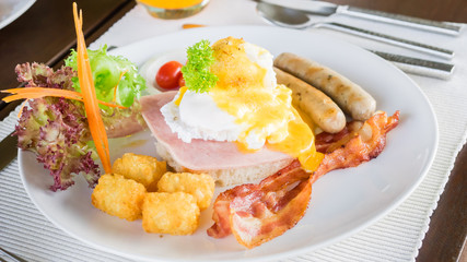 Egg benedict  on ham with bacon, sausage and vegetable for breakfast.
