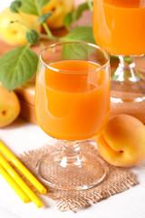 succo di albicocca sul tavolo bianco con frutta fresca intorno