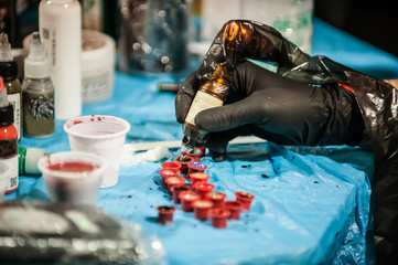 Tattoo Artist. Tattooist with protective gloves filling needle with color inks. Closeup