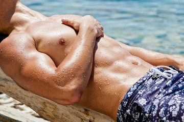 Young sexy wet guy lying on the beach