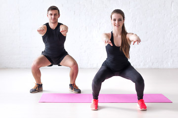 Fitness man and woman exercising squat exercise hands behind