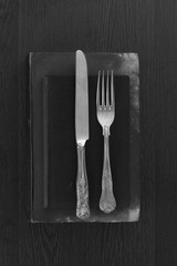 Vintage cutlery on old books in black and white setting