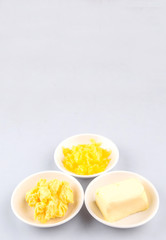 A block of butter, margarine and ghee in white bowls