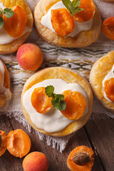 Apricot cakes with cream and mint close-up vertical top view
