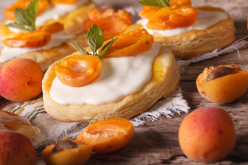 Apricot pastries with soft cream and mint close-up horizontal