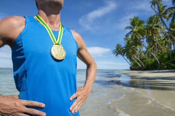 First place Brazilian athlete standing with gold medal on empty beach