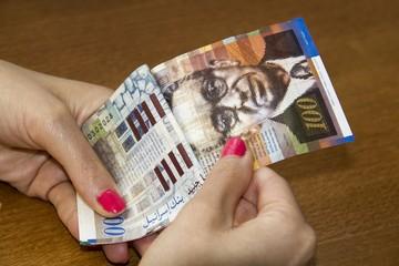 Woman counting money - Israeli New Sheqel banknotes.