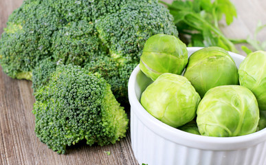 Brussels sprouts and broccoli, fresh vegetables on wooden background