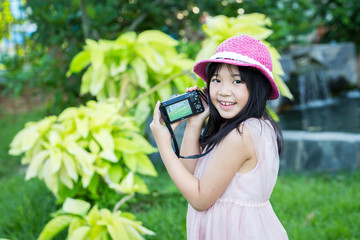 Little asian cute girl showing picture in screen of camera in park