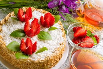 Celebratory cake with strawberries flowers, tea and irises