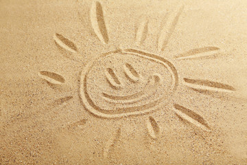 Drawing sun on beach sand