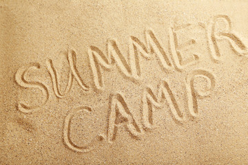 Summer camp handwritten in a beach sand